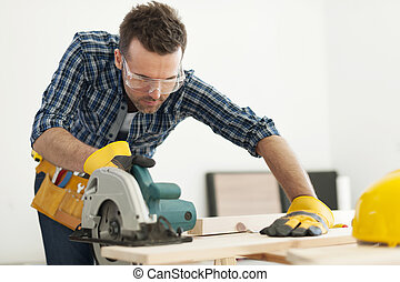 Focus carpenter sawing wood board
