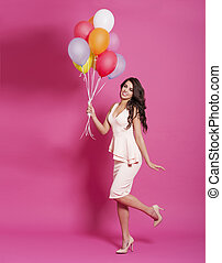 Fashion woman with balloons on pink background