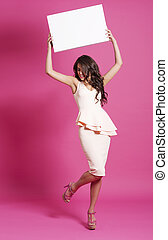 Fashion model holding blank board above her head