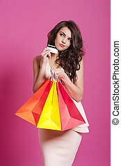 Confused attractive woman with credit card and shopping bags