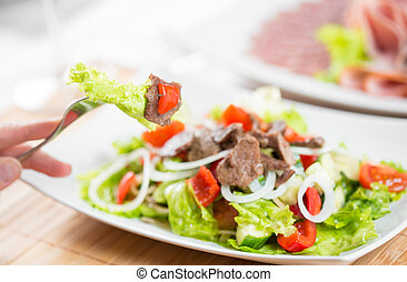 Hand with fork and vegetable salad with beef meat