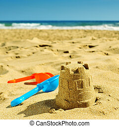 summer on the beach, with a retro effect - a sandcastle and...