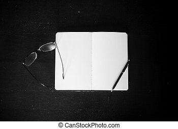 Eyeglasses with notepad and pen on the table