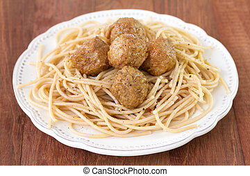 meatballs with spaghetti in plate on brown background