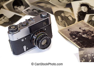 The old film camera and ancient photos on a white background...
