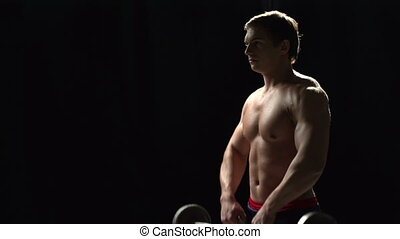 Weight Training - Sideway shot of bodybuilder performing...