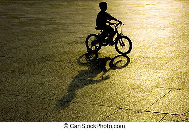 kid riding bicycle silhouette in sunset