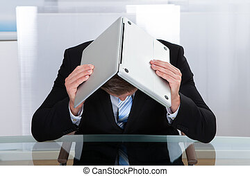 Depressed businessman hiding under his laptop - Depressed...