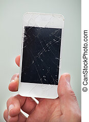 Businessman holding a damaged smartphone with a smashed...
