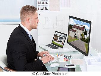 Businessman checking a property portfolio online -...