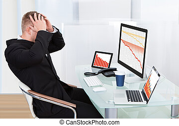 Despairing businessman faced with financial losses sitting...