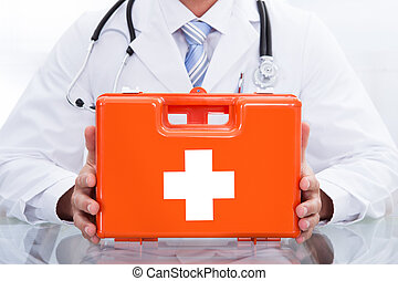 Smiling doctor or paramedic with a first aid kit - Smiling...