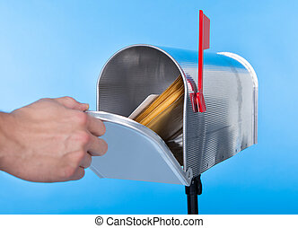 Man opening his mailbox to remove mail inside close up of...