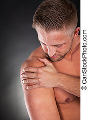 Muscular sportsman massaging his shoulder - Muscular...