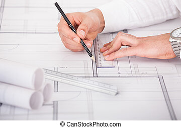Architect Working On Blueprint Design - Cropped image of...