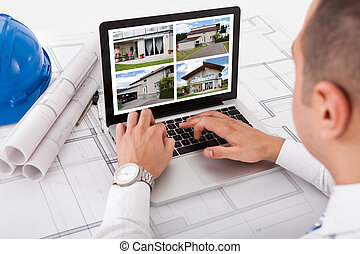 Architect Looking At Designs Of House On Laptop - Male...