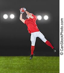 American Football Player Jumping On Field