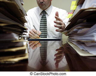 Businessman at Desk with Files Gesturing - Businessman...