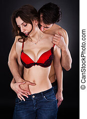 Man Inserting Hand In Womans Jeans While Kissing On Neck -...