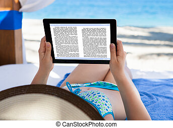 Woman Reading E-Book At Beach - Woman reading e-book in...