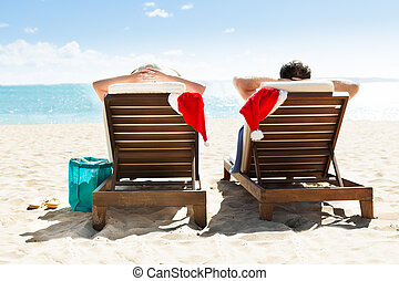 Couple with Santa hats relaxing on deck chairs at beach...