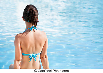 Woman Sitting At The Edge Of Swimming Pool
