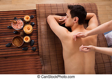 Young Man Receiving Back Massage In Spa - High angle view of...