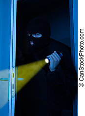 Thief Holding Flashlight While Entering Into House - Thief...