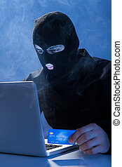 Hacker Holding Credit Card While Using Laptop - Hacker...