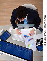 Businessman Examining Graphs At Desk - High angle view of...
