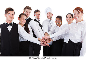 Waiters and waitresses stacking hands. Isolated on white