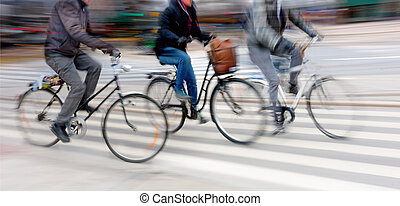 Three cyclists at high speed in blurred motion in city