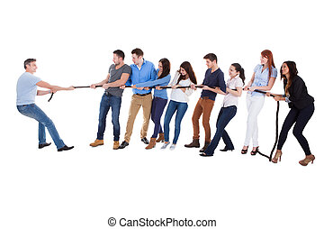Group of people having a tug of war against one man as they...