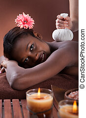 Woman Enjoying Herbal Massage At Spa - Side view of African...