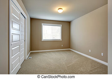 Empty beige room with window, closet and capret floor