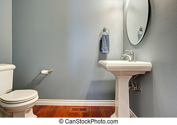 Simple grey bathroom VIew of white toilet and washstand