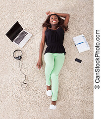 Woman Relaxing On Rug At Home