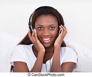 Woman Enjoying Music Through Headphones In Bed - Happy...
