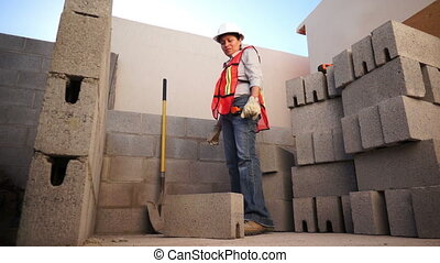 Woman Lifts Brick on Construction S - Low angle shot of a...