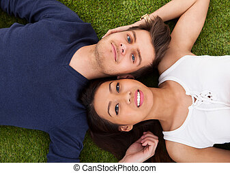 Young Couple Lying On Grass - Directly above shot of young...