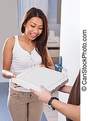 Woman Receiving Pizza From Delivery Man - Smiling young...