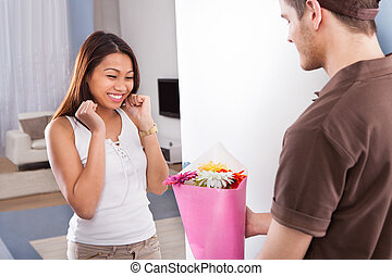 Woman Receiving Bouquet From Delivery Man - Happy young...