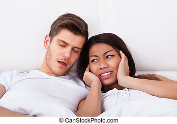 Irritated Woman Covering Ears While Man Snoring In Bed -...