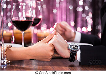 Couple Holding Each Others Hand At Dinner - Romantic Couple...