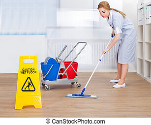 Happy Maid Cleaning Floor With Mop - Portrait Of Young Maid...