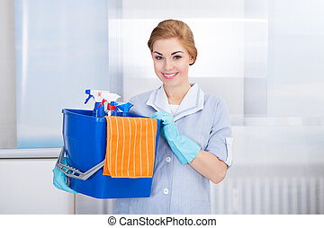 Young Maid Holding Cleaning Supplies - Happy Young Maid...