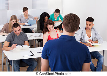 Teacher Teaching University Students - Rear view of teacher...
