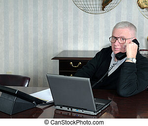Working Senior Businessman - A senior businessman talking on...