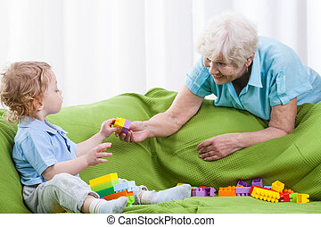 Grandmother playing with grandson - Grandmother cheerfully...