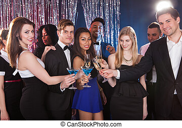 Happy Friends Toasting Drinks At Nightclub - Portrait of...